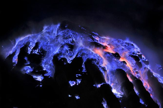 Escaped at gaseous state from the Kawah Ijen crater on Java Island in Indonesia sulfur combusts on contact with air, liquefies and run in impressive rivers of blue flames. Indon sie